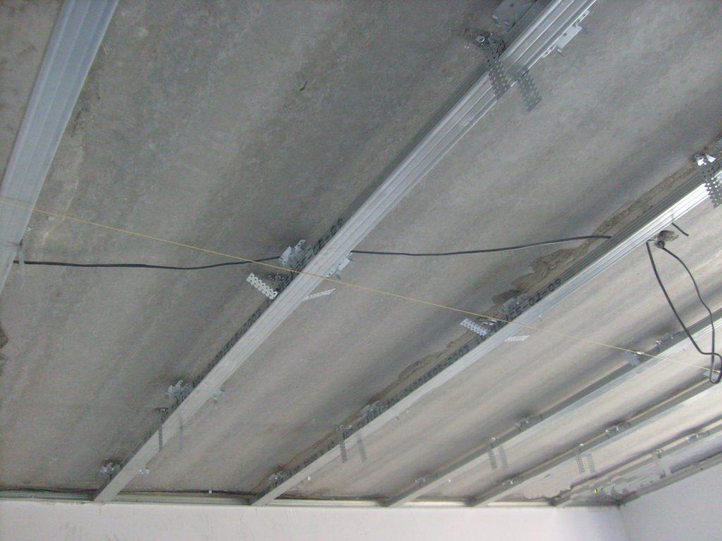 Первое, что надо сделать - установить металлический каркас будущего потолка