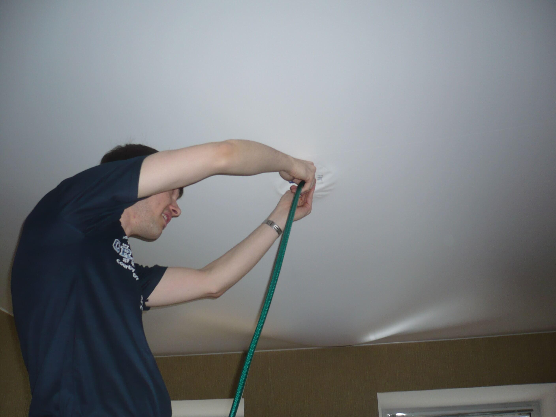 Слив воды из натяжного потолка при помощи шланга