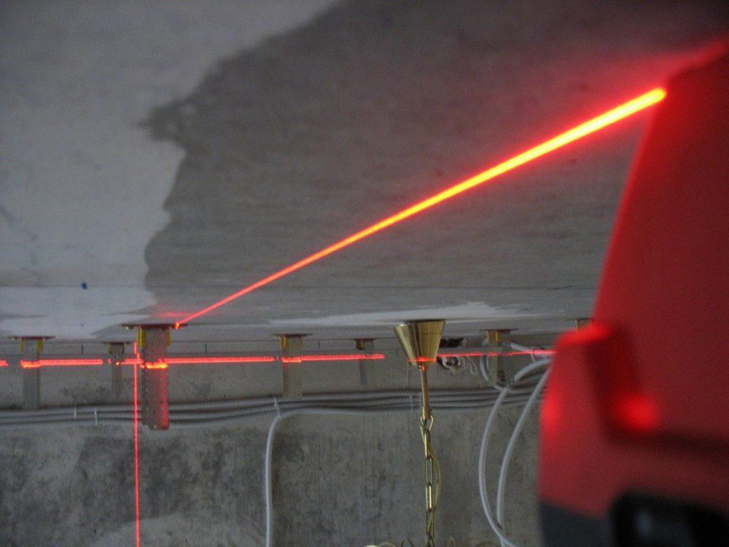Разметка потолка производится лазерным или водяным уровнем